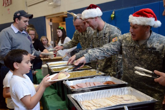 New York Army National Guard Col. Phil Pugliese, Chief of Staff of the 42nd Infantry Division dishes out turkey to a family member during the division headquarters' annual holiday dinner and party on Sunday, Dec. 2.