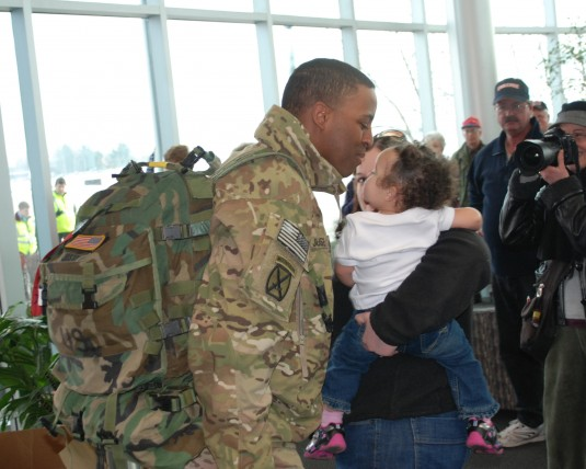 Sgt. 1st Class Antoine Juste greets his wife Mary and twin daughters