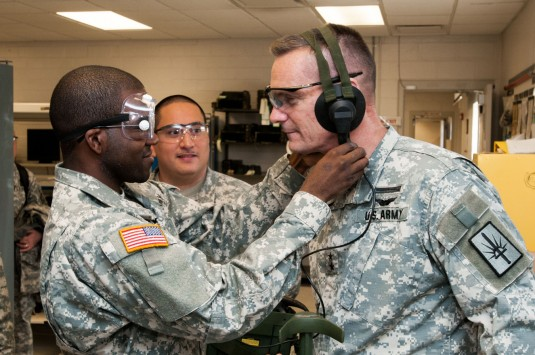 New York Army National Guard Private First Class Joseph Myers, Brooklyn, New York, 145th Surface Maintenance Company, New York National Guard adjusts a mine detector headset for Major General Patrick A. Murphy, the Adjutant General of New York during his