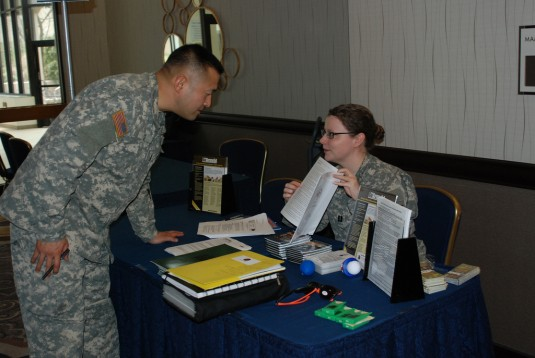 Capt. Ashlee Coye provides educational material to 1st Lt. Steven Oh from the 27th Infantry Brigade Combat Team during the unit