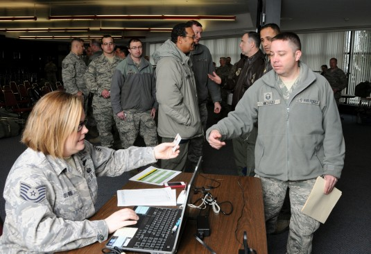 Airmen of the 105th Airlift Wing check-in at the deployment processing station during an initial winter storm response here March 18, 2013.The 20 Airmen will stand by with five humvees to assist local governments in the Hudson Valley if needed when a snow
