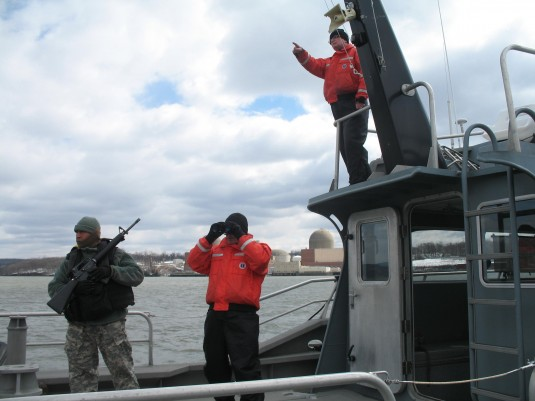 New York Army National Guard Sgt. Ivan Martinez, joins New York Navasl Milita members Petty Officer  Steve Gauci and Petty Officer Jeff Alexander (on top of the cabin) on board Naval Militia Patrol Boat 400 off Indian Point Energy Center on March 22. The