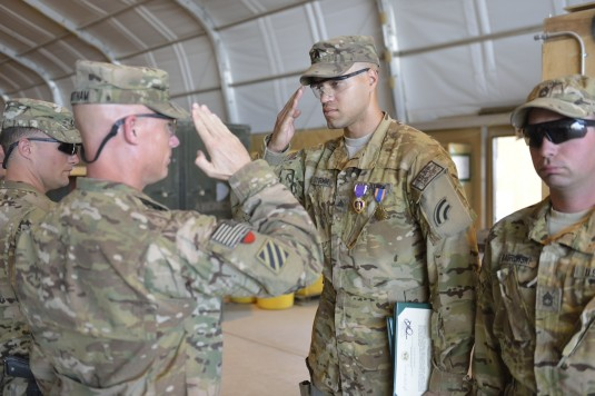 New York Army National Guard Sgt. John Stormm, a member of Detachment 1 Company B 3rd Battalion 126th Aviation (Heavy Lift) receives the Purple Heart and the Air Medal from Lt. Col.  Mike Higginbotham, the commander of Task Force Knighthawk during award c