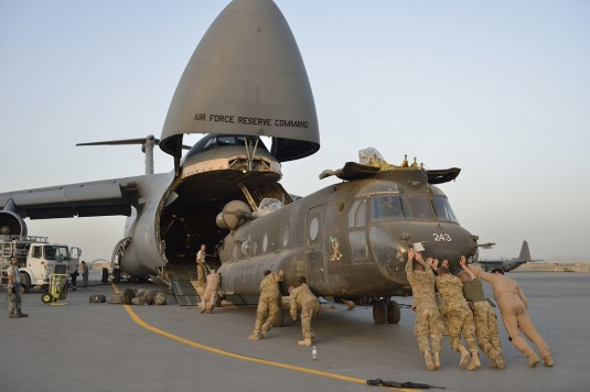 New York Army National Guard Soldiers assigned to Rochester's Detachment 1, Company B, 3rd Battalion 126th Aviation (Heavy Lift) load CH-47 helicopters onto a C-5 Galaxy as they prepare to return home to the United States following a nine-month depl