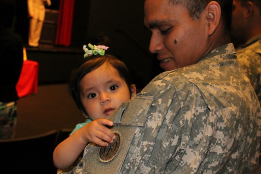 Spc. Frankie Aguilar of the 1st Battalion, 69th Infantry Regiment watches as his daughter Jadalyse plays with his unit patch during a Freedom Salute Ceremony April 28