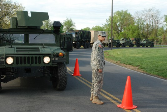 Army National Guard Spec Andrew Oliver directs traffice around vehicles assigned to the 206th Military Police Company outside Division of Military and Naval Affairs Headquarters on Thursday, May 9. The company was lining up vehicles to prepare for a road