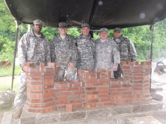 New York Army National Guard Soldiers of the 1156th Engineer Company stand behind their final project here, a replica engineer castle
