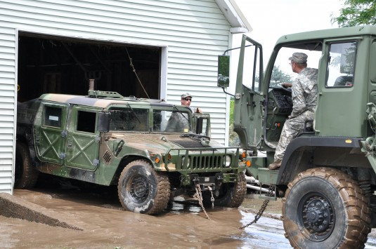 New York Army National Guard Soldiers Staff Sgt. Gary Matt from the 2nd Battalion 108th Infanty and Staff Sgt. Joe Bolton from the 206th Military Police Company tow a surplus humvee used by the Village of Mohawk as a rescue vehicle out of a garage where i