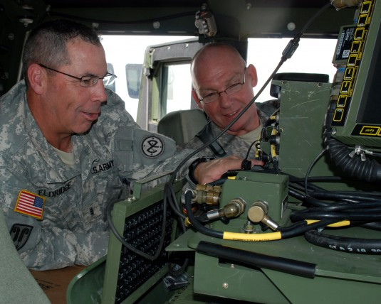 Chief Warrant Officer 3 Charles Eldridge (left), assigned to the 27th Infantry Combat Brigade Team assist Master Sgt. William Yohn of the 42nd Infantry Division install secure communications data