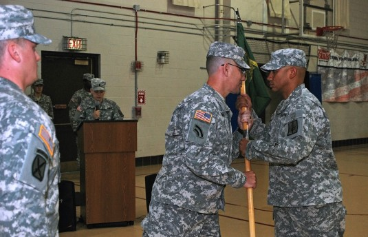 102nd Military Police Battalion Commander Lt. Col. Arthur Zegers (center) passes the 206th Military Police Company guidon to Capt. Carlos Nazario (right), signifying Nazario's assumption of command of the company in a ceremony here July 9.