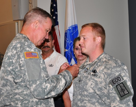 New York Army National Guard Sgt. Joshua Young, a member of the 1108th Ordnance Company (Explosive Ordnance Disposal) recieves the Bronze Star with V device for valor during a ceremony at the Scotia-Glenville Armed Forces Reserve Center here on Friday, Ju