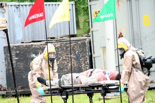Soldiers from the decontamination element of the Chemical Biological Radiological and Nuclear enterprise prepare a simulated casualty for decontamination during a disaster response exercise