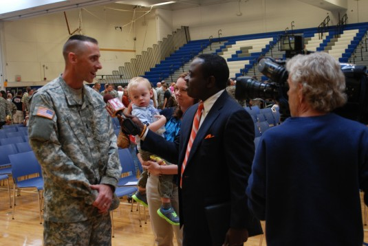 WNYT-TV newsman Dan Bazile interviews New York Army National Guard Lt. Christopher Stockton, a Ballston Lake resident and a member of the 42nd Combat Aviation Brigade, during the brigade's farewell ceremony at Shaker High School here on Saturday Sept.