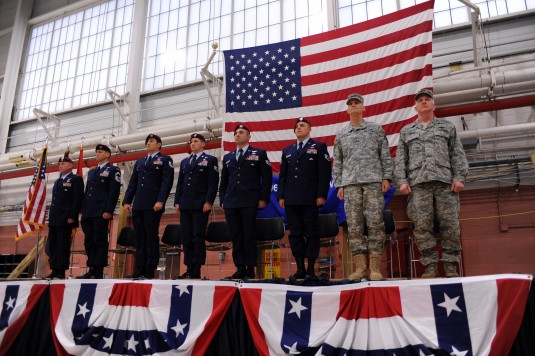 Major General Patrick Murphy, the Adjutant General of New York, and Col Thomas Owens, the commander of the 106th Rescue Wing stand at attention with six members of the 103rd Rescue Squadron who received the Bronze Star with V for Valor during an award cer