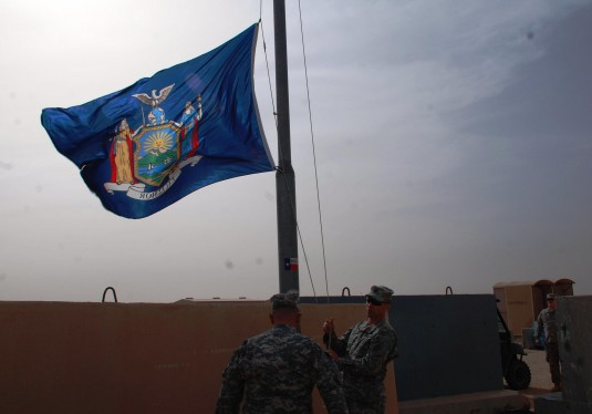 New York Army National Guard Lt. Col. Jack James, the commander of the 642nd Aviation Support Battalion and Battalion Command Sgt. Major Mark Wilson raise the New York state flag above the battalions headquarters here on Saturday, Dec. 14 as the battalion