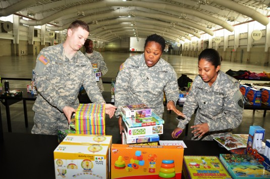 Soldiers from the New York  Army National Guard 369th Sustainment Brigade, and 222nd Chemical Company  take a break from sorting toys on Thursday, Dec. 19, at the Javitts Convention Center, as they assist Governor Andrew Cuomo's office and the New Yor