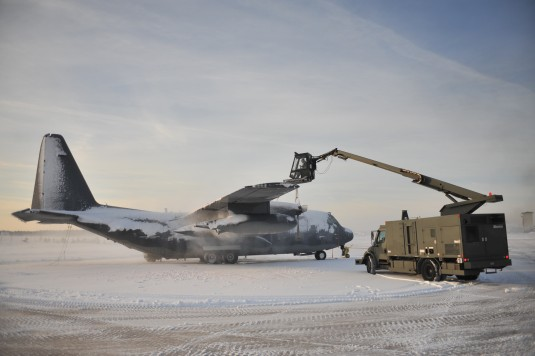Airmen from the 106th Rescue Wing Civil Engineering Squadron de-ice an HC-130 at F.S. Gabreski ANG on February 4th 2014 following a heavy snowstorm the evening before