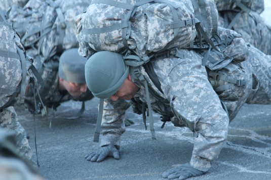 Soldiers of the 42nd Infantry Division's Headquarters and Service Company get in the right mood for a two-mile ruck march they conducted during drill here on Friday February 8 as part of the February drill weekend by doing push ups with full field pac