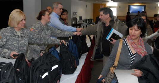 New York Army National Guard Sgt. Pamela Daigle (left) and Sgt. 1st Class Karin Tirinato (right) distribute disaster and emergency response starter kits following a session of New York Governor Andrew Cuomo's Citizen Preparedness Corps Training Progra