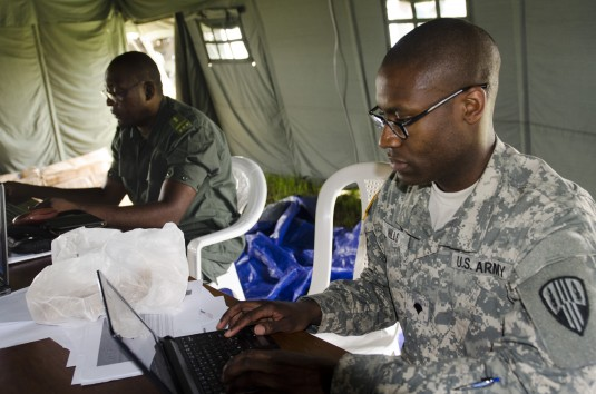Congolese national police Capt. Patrick Ossate and New York Army National Guard Specialist  Daren E. Mills, a member of the 369th Sustainment Brigade, process Soldiers arriving at Exercise Central Accord 14 in Douala, Cameroon, March 18.