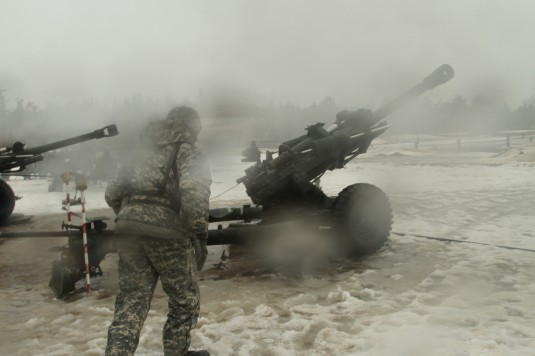 A soldier with Battery A, 1st Battalion of the 258th Field Artillery Regiment, runs toward Gun 5 moments after it fired in the rain and snow at Fort Drum, N.Y. April 5.