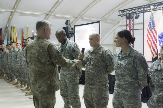 New York Army Natonal Guard Soldiers from the 42nd Combat Aviaton Brigade speak to Command Sgt. Major of the Army  Raymond F. Chandler III during a visit to Kuwait. The Soldiers received his coin in recognition of their outstanding work.