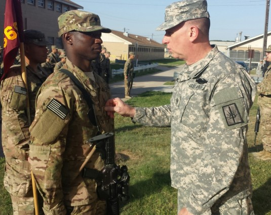 New York Army National Guard Command Sergeant Major Frank Wicks (right) promotes 1569th Transportaton Company member Ronald Walker to sergeant during a visit to the unit on April 29. The 1569th Soldiers have been training at Fort Drum to prepare for deplo