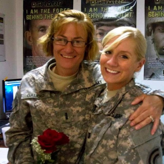 New York Army National Guard Captain Capt. Noelle Helgeson presents a flower to Chief Warrant Officer 4 Renee Gaudio on Mothers Day, May 11. Moms assigned to the 42nd Combat Aviation Brigade headquarters received carnations to mark the day and their seper