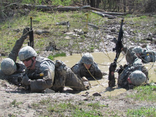 New York Army National Guard Soldiers from the Auburn, N.Y.-based 102nd Military Police Battalion react to direct fire and prepare to assault the enemy during a pre-mobilization training fight lane exercise Sunday, May 11 at Fort Drum.