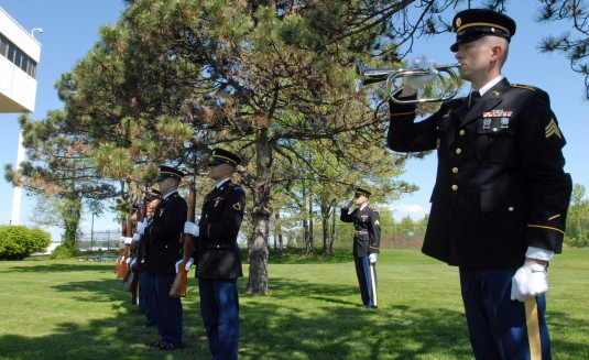 New York Army National Guard Soldier Sgt. Charles Holmes (right) plays Taps while a firing detail presents arms (left ) during a Memorial Day Ceremony held at the New York State Division of Military and Naval Affairs here May 20 2014. More than 200 person