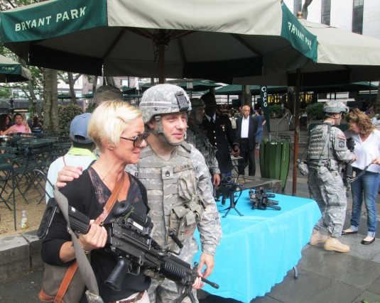 ew York Army National Guard Staff Sgt. Daniel Dukin poses with a visitor to the weapons and equipment display the 1st Battalion 69th Infantry presented in Bryant Park on Friday June 13 as part of events commemorating the 239th Birthday of the United State