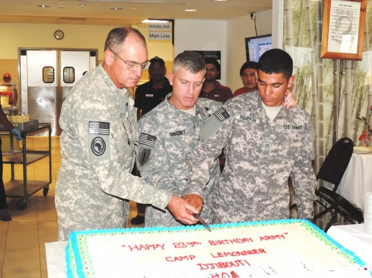 New York Army National Guard Warrant Officer Dave Lewis ( left) joins Brig. General  Wayne Grigsby, commander of Combined Joint Task Force- Horn of Africa and a Soldier from the 1st Battalion 18th Infantry in cutting an Army Birthday cake on Saturday June