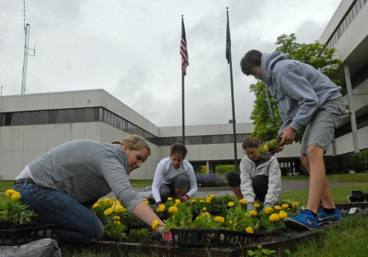 Keri ONeil (left) Colleen Casey (middle left) Lisa Hedges (middle right) and her son Jacob Hedges (far right) plant a bed of marigolds at the New York State Division of Military and Naval Affairs (DMNA) here June 11. The planting which resembles the shape