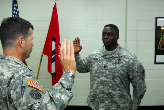 Lt. Col. Christopher Panzer, commander of Headquarters and Headquarters Battalion of the 42nd Infantry Division reenlists the battalion Command Sgt. Major Anthony McLean during a drill at the Glenmore Road Armory. McLean, who has served in the Army since