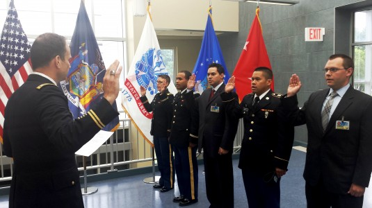 Lt. Col. Stephen Howe, the Senior Army Advisor to the New York Army National Guard, administers the oath to five new officers during a short ceremony here in Latham.