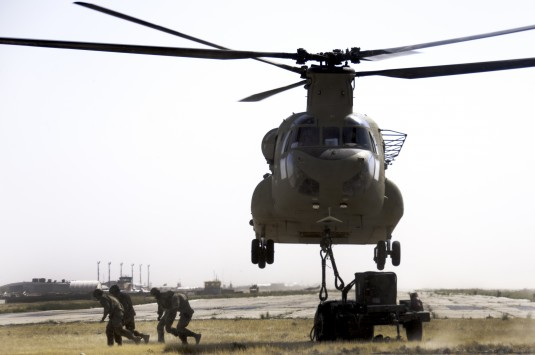 -Soldiers assigned to the New York Army National Guard's 1569th Transportation Company make their way out from under the Chinook. As soon as the instructors ensured the cargo was hooked up, they would signal to the crew team that everything was ready