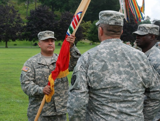 Col. Dave Martinez holds the colors of the 369th Sustainment Brigade during formal Change-of-Command ceremonies here on Sunday, August 3. Martinez took command of the brigade from Lt. Col. James Gonyo the Deputy Brigade Commander.