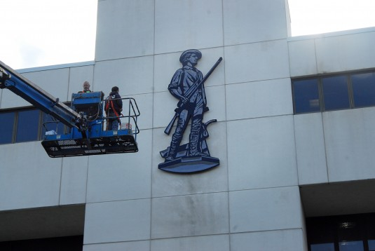 Workers finish mounting a 15-foot high National Guard minuteman on the walls of the Division of Military and Naval Affairs headquarters building here on Thursday, Oct. 9. The new logo identifies the building as the headquarters of the New York National Gu
