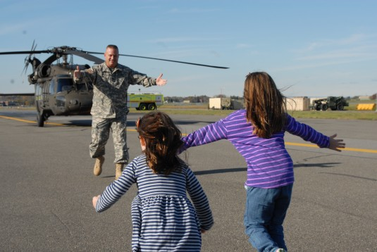 New York Army National Guard Col. Al Ricci greets his daughters following his final flight as a military pilot on Monday Oct. 27 at the Army Aviation Support Facility here. Ricci, a veteran of the Iraq War is retiring after 30 years. His final service was