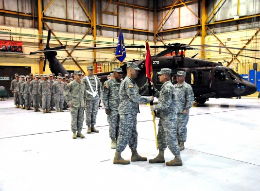 LATHAM-- New York Army National Guard Lt. Col. Jack James accepts the colors of the 42nd Combat Aviation Brigade from Major General Harry Miller, commander of the 42nd Infantry Division, during change-of-command ceremonies at the Army Aviation Support Fac