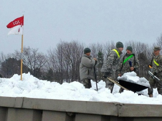 New York Army National Guard Soldiers troopers from A Troop, 2nd Squadron, 101st Cavalry, based in Niagara Falls, New York, conduct snow removal operations from the roof of the Eden Heights Assisted Living Facility in West Seneca, New York November 23. So