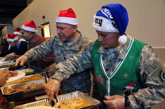42nd Infantry Division Chief of Staff Col. Phil Pugliese (right) and Command Sgt. Major David Piwowarski, dish out Christmas Dinner to division members and their families on Sunday, Dec. 7 during the annual holiday festivities at division headquarters at