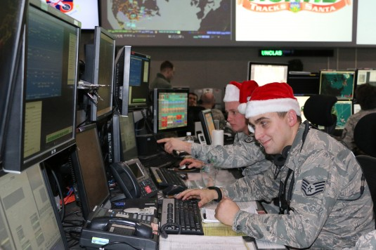 New York Air National Guard Staff Sgt. Nicholas Tharrett, pointing, and Staff Sgt. Andrew Washburn train for Christmas Eve tracking operations at the Eastern Air Defense Sector in Rome, N.Y. Each year the North American Aerospace Defense command (NORAD) h