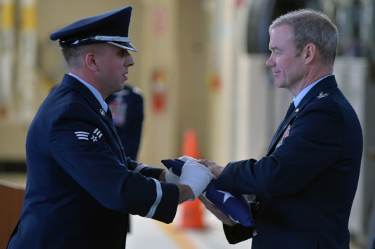 106th Rescue Wing Operations Group Commander Colonel Brian Rex Reilly accepts a folded American flag during his retirement ceremony from the New York  Air National guard at FS Gabreski Air National Guard Base on Jan. 11 2015. Col. Reilly retires following