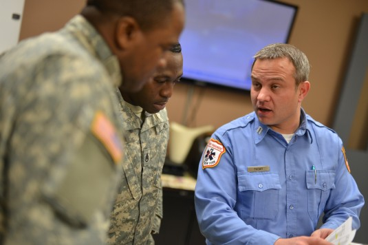 New York Army National Guard Staff Sergeants Adrian McLaughlin and Kehinde Ayeni discuss the deployment of National Guard vehicles and crews with New York Fire Department Captain Joseph Pataky on Monday Jan 26 2015.
