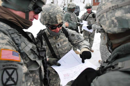 New York Army National Guard 1st Lt. Yvette Valle assists her group in starting to plot out points on the map they were just given in preparation for a snowy land navigation course at Camp Smith Training Site on Feb. 23. Valle is among a group of 42nd Inf