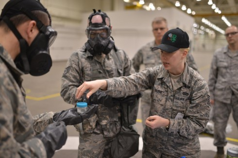 Technical Sergeant Lindy Ross, a member of the New York Air National Guard's 106th Rescue Wing demonstrates how to prepare a sample of an unidentified substance for testing during a training scenario at Global Dragon deployment for training at the Gu
