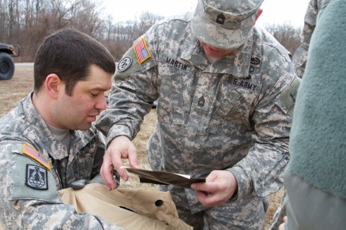 New York Army National Guard Sgt. Andrew Mesick, left, of the Headquarters and Headquarters Company of the 42nd Combat Aviation Brigade, helps Master Sgt. Gregory Martin repair part of a Command Post Tent System during training event at the Guilderland Ra