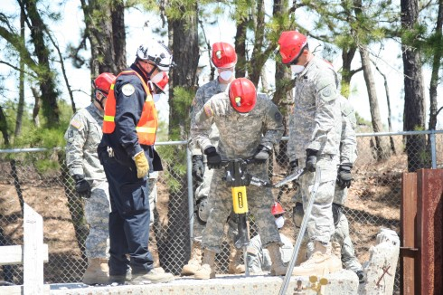 Pfc. Dandy Beverly uses a jack hammer to break through reinforced cement under the guidance of New Jersey Task Force One urban search and rescue instructor Bob McDermott