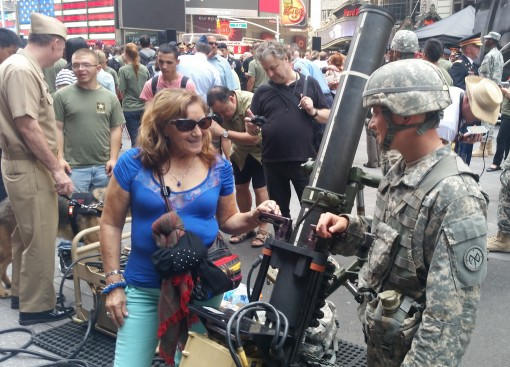 New York Army National Guard Spc. Harrison Wang, a member of the 1st Battalion 69th Infantry Battalion, explains the mechanics of the 120 mm mortar system to a visitor to the Army 240th  Birthday celebration on Friday, June 12 in Times Square. The 69th In